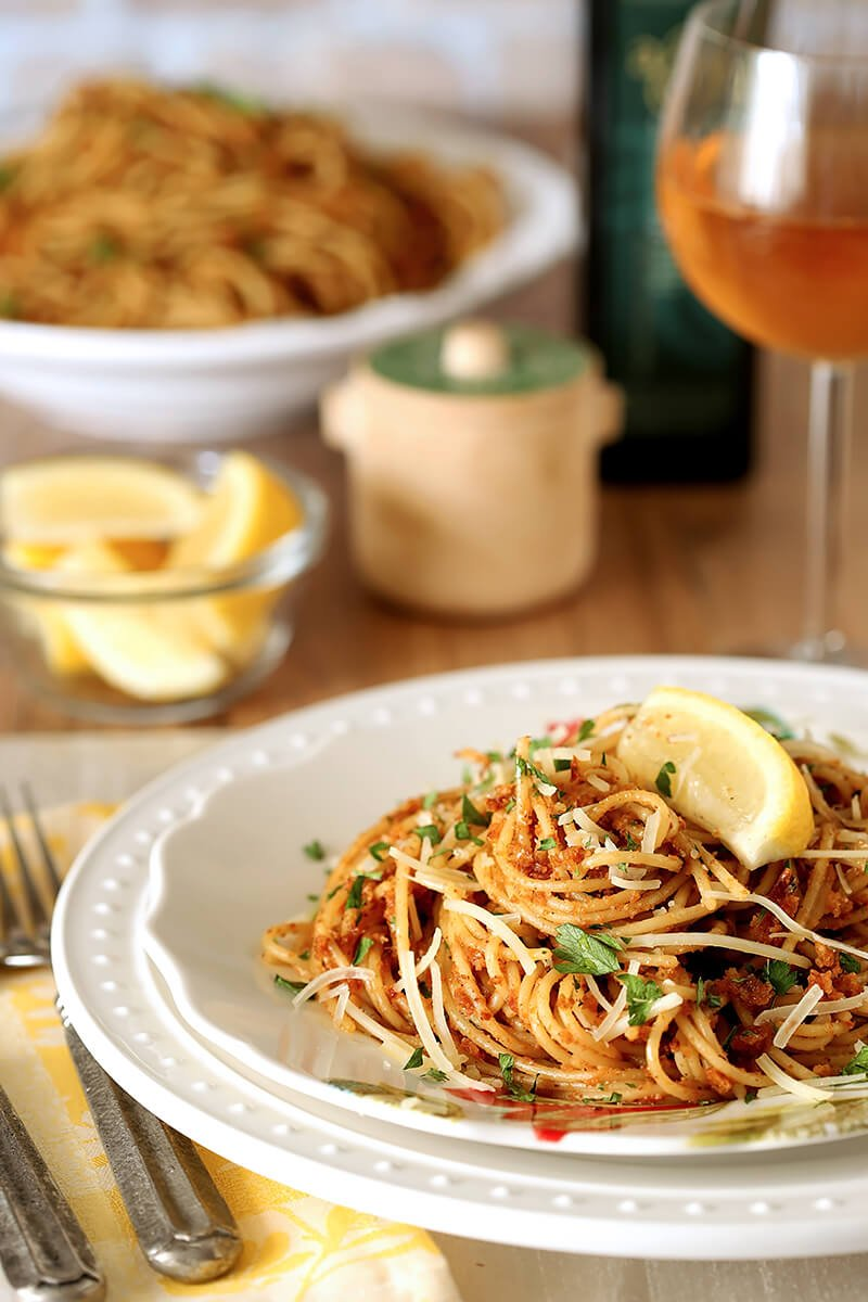 Pasta with Sun-Dried Tomato and Roasted Almond Pesto Served on a White Plate with Lemon Garnish