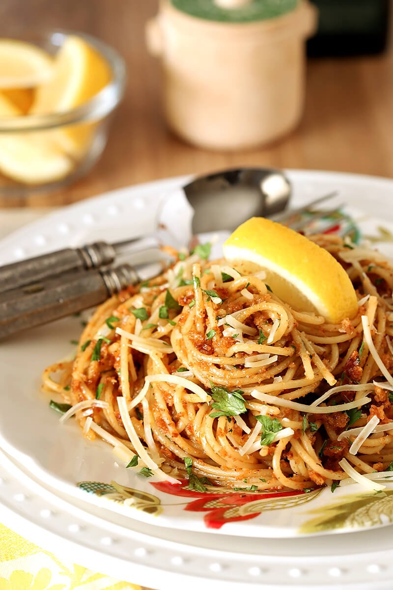 Plate of Pasta with Sun-Dried Tomato and Roasted Almond Pesto with a Lemon Garnish