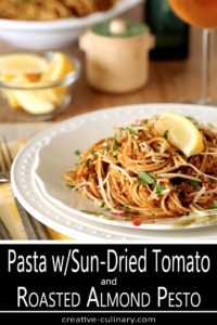 Serving of Pasta with Sun-Dried Tomato and Roasted Almond Pesto Served on Round White Decorative Plate
