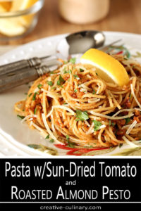 Pasta with Sun-Dried Tomato and Roasted Almond Pesto Garnished with Lemon and Basil on White Decorated Plate