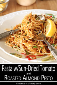 Fork Twirled with Pasta with Sun-Dried Tomato and Roasted Almond Pesto on White Decorated Plate