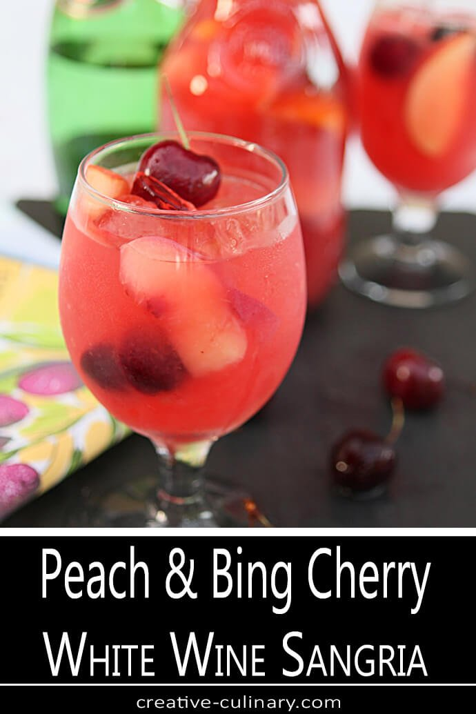A White Wine Sangria with Peaches, Cherries, Apple and Oranges in a Wine Glass Garnished with a Bing Cherry