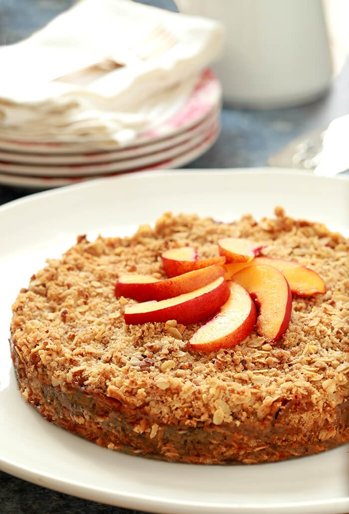 Fresh Double Crusted Peach and Pecan Crisp on a White Serving Plate Garnished with Peach Slices