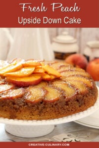 Fresh Peach Upside Down Cake on a White Cake Platter with More Peaches as Garnish