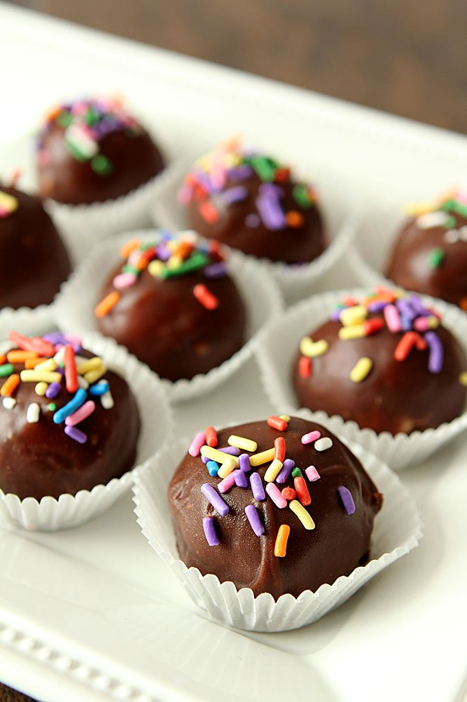 Peanut Butter Coconut Balls covered in chocolate and assorted jimmies are served on a white tray in white paper candy cups.