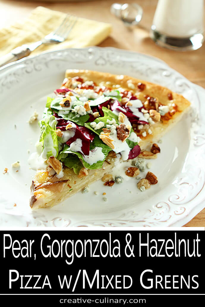 Pear Gorgonzola and Hazelnut Pizza Slice with Mixed Greens on a White Plate.