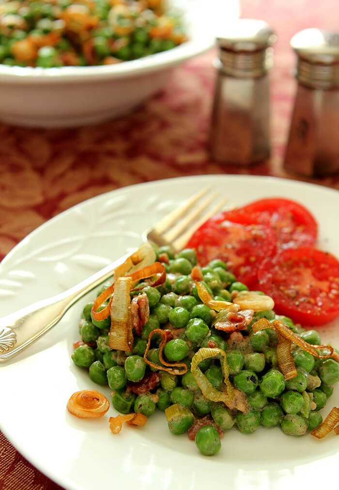 Peas with Bacon and Leeks Served on a White Plate with Fresh Tomato Slices