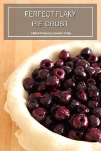Perfect Flaky Pie Crust Laid Out Over a Pie Plate that is Filled with Cherries