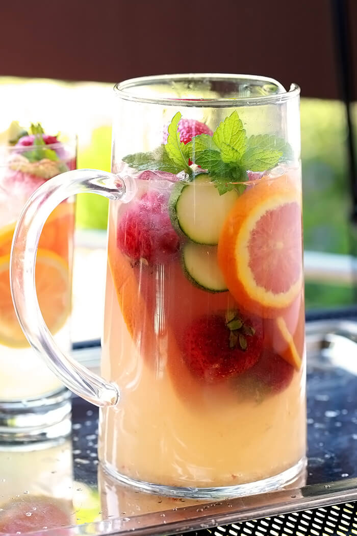 The Pimm's Cup Cocktail in a Pitcher with Fruit and Cucumber Slices