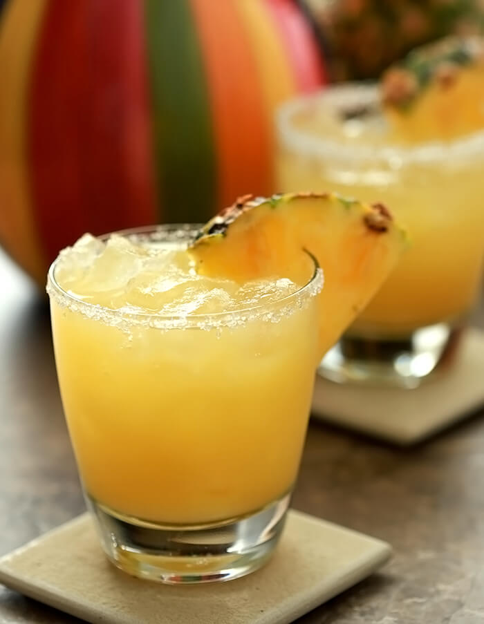 Fresh Pineapple Margarita Cocktails garnished with wedges of pineapple.