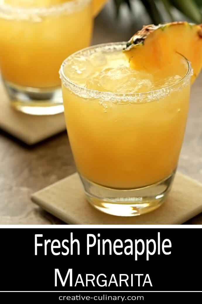 Fresh Pineapple Margarita in a lowball glass with a salt/sugar rim and garnished with a pineapple wedge.