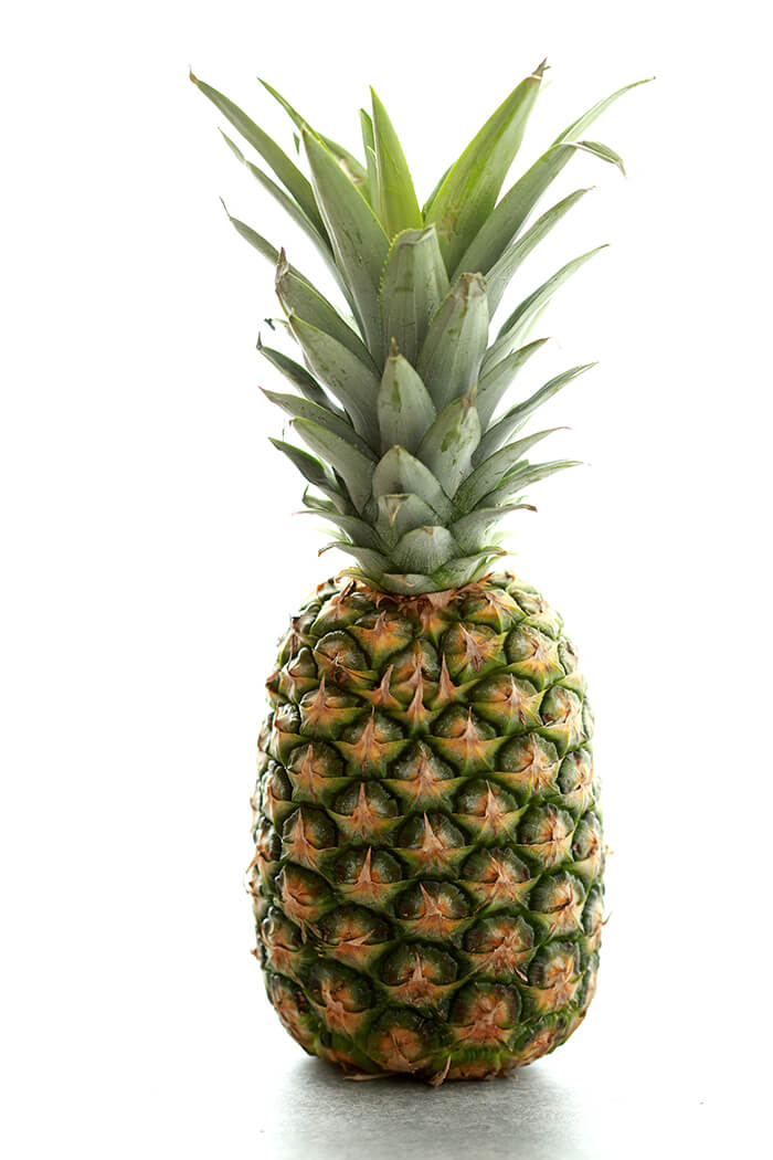 Fresh Pineapple photographed standing vertically.