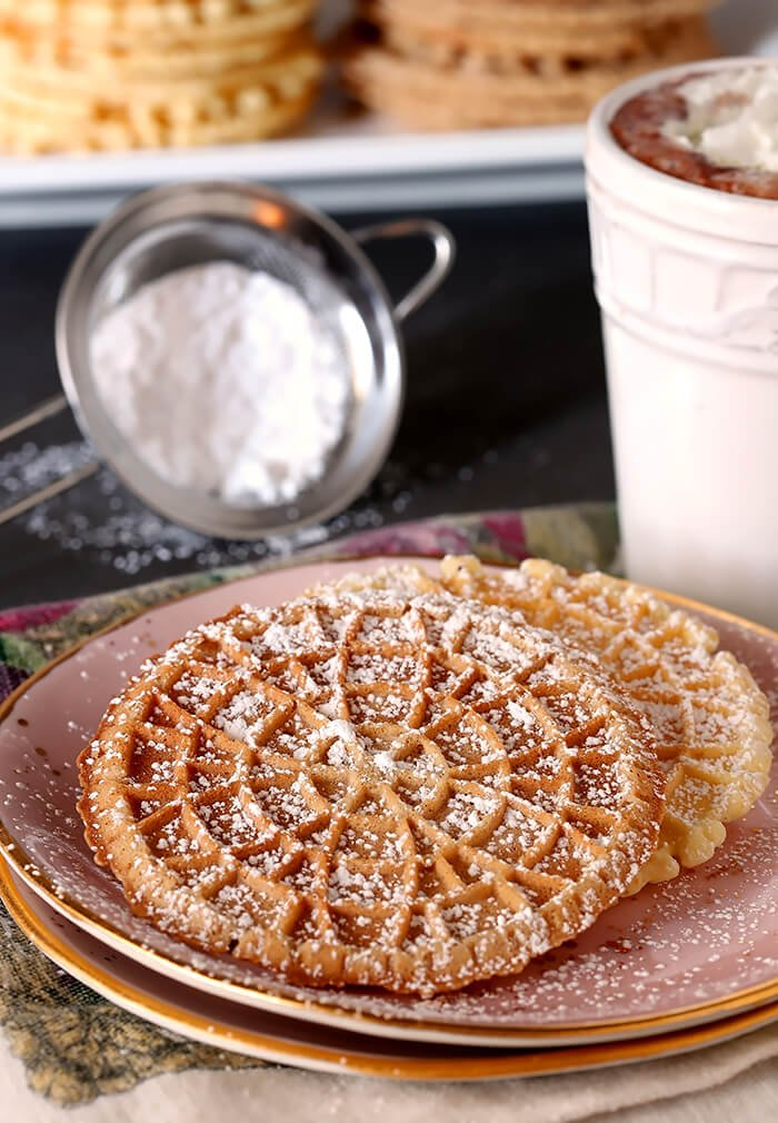 Pizzelles - Italian Waffle Cookies Sprinkled with Powdered Sugar and Served on Pink Plate