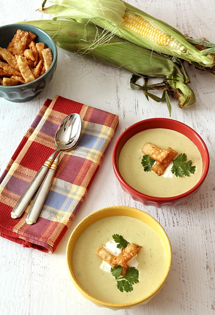Two Bowls of Roasted Poblano Pepper and Corn Soup in Yellow Bowl Garnished with Tortilla Strips