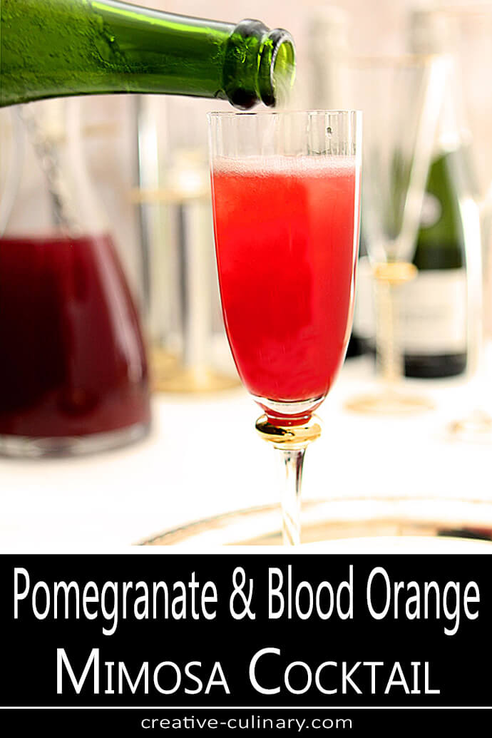 Pomegranate and Blood Orange Mimosa Cocktail in a Glass with Prosecco Being Poured PIN