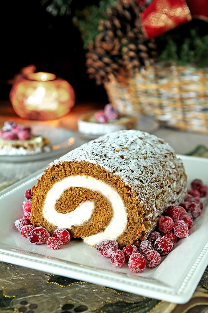 Pumpkin Roll with Cream Cheese Filling on a White Serving Plate and Garnished with Sugared Cranberries