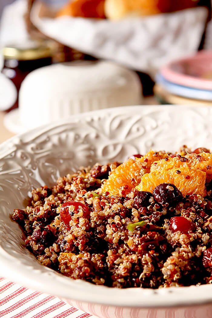 Quinoa Salad with Oranges, Pecans and Cranberries Served in a White Bowl on a Red and White Tablecloth