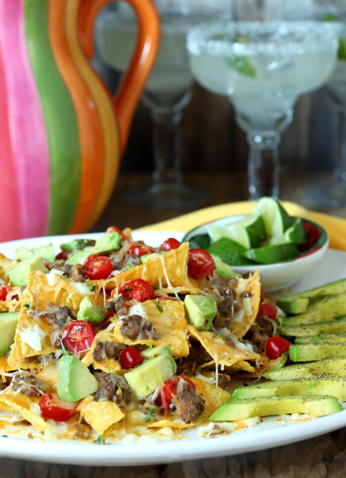 Plate of Refried Bean and Beef Nachos with Lime Wedges