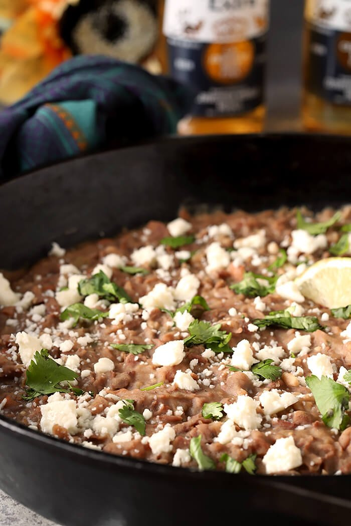 Queso Fresco Cheese and Cilantro Garnish a Cast Iron Skillet Filled with the Best Homemade Refried Beans