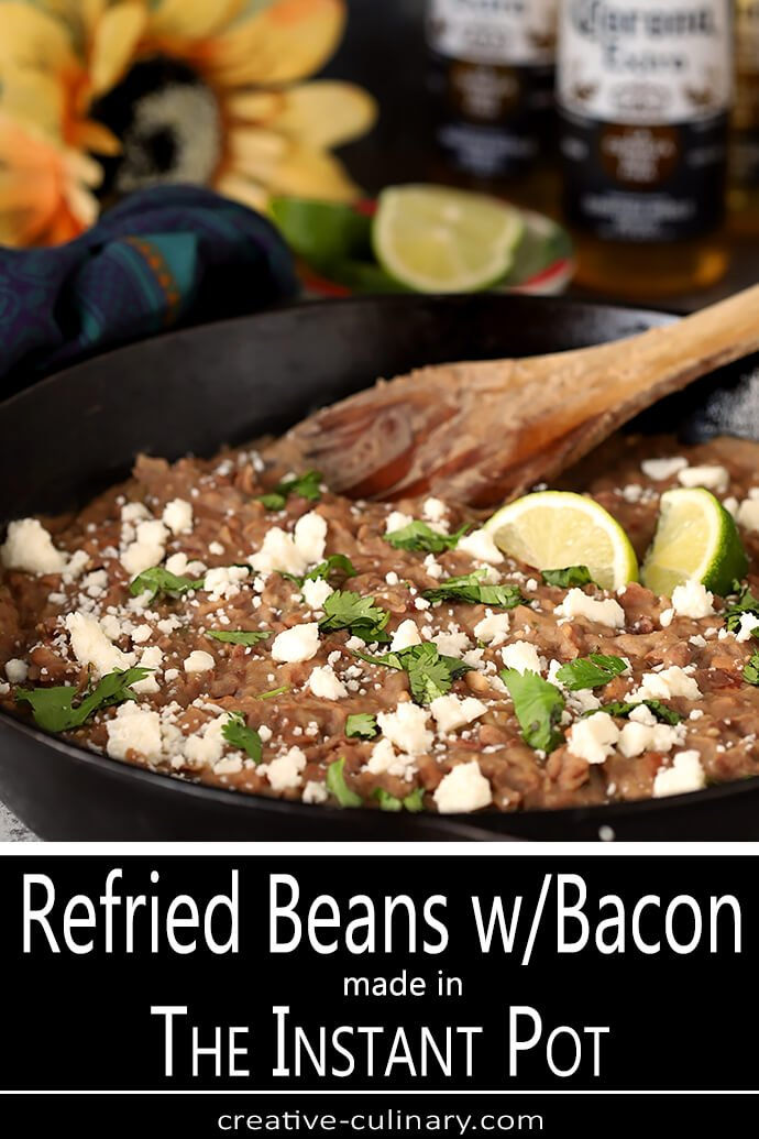 Queso Fresco Cheese and Cilantro Garnish a Cast Iron Skillet Filled with the Best Homemade Refried Beans with Bacon