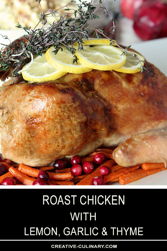 Whole Roast Chicken Leg with Lemon, Garlic, and Thyme on Platter with Carrots and Cranberries