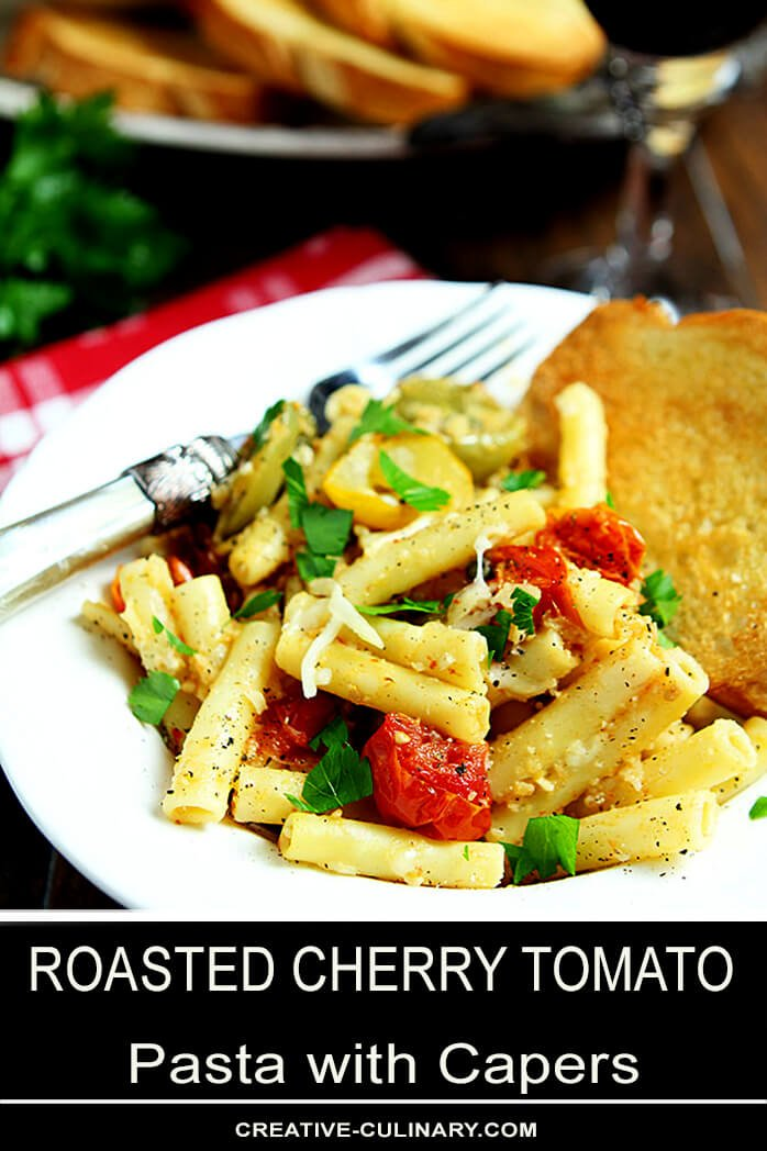 Roasted Cherry Tomato Pasta with Capers Served on a White Plate with Garlic Toast