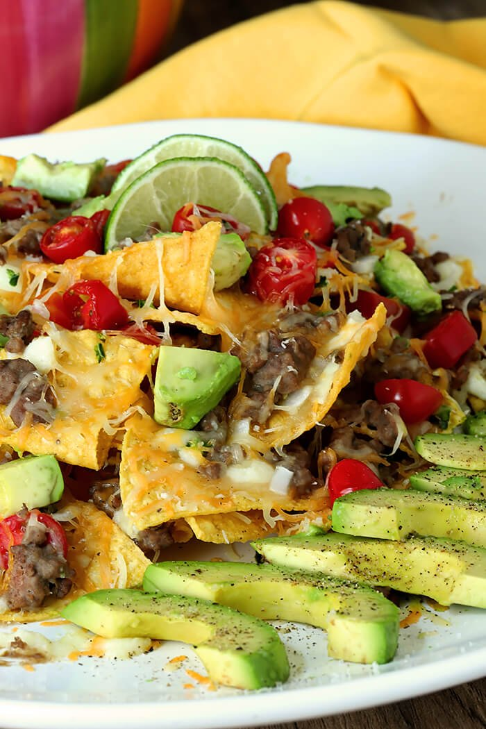 Closeup of Refried Bean and Beef Nachos with Lime Wedges