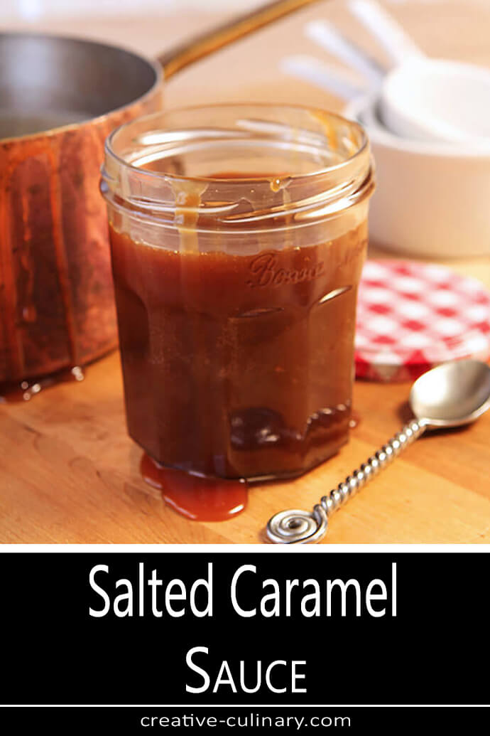 Jar of Homemade Salted Caramel Sauce Sitting Next to a Copper Pan with a Decorative Spoon on the Table PIN