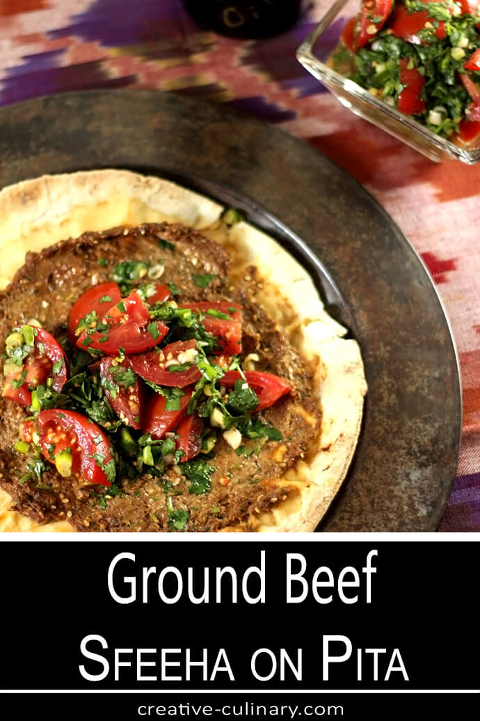 Ground Beef Sfeeha on Pita on Metal Plate with Tomato and Parsley Salad