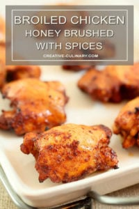 Broiled Honey Brushed Chicken Thighs with Spices on a White Rectangular Serving Dish