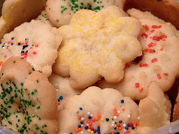 Old Fashioned Spritz Butter Cookies Piled in a Holiday Tin