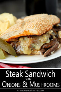 Steak and Cheese Sandwich with Caramelized Onions and Mushrooms Served on a White Plate with Dill Pickles and Chips