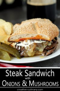 Steak and Cheese Sandwich with Caramelized Onions and Mushrooms Topped with Horseradish Mayo and Served on a White Plate with Pickles and Chips