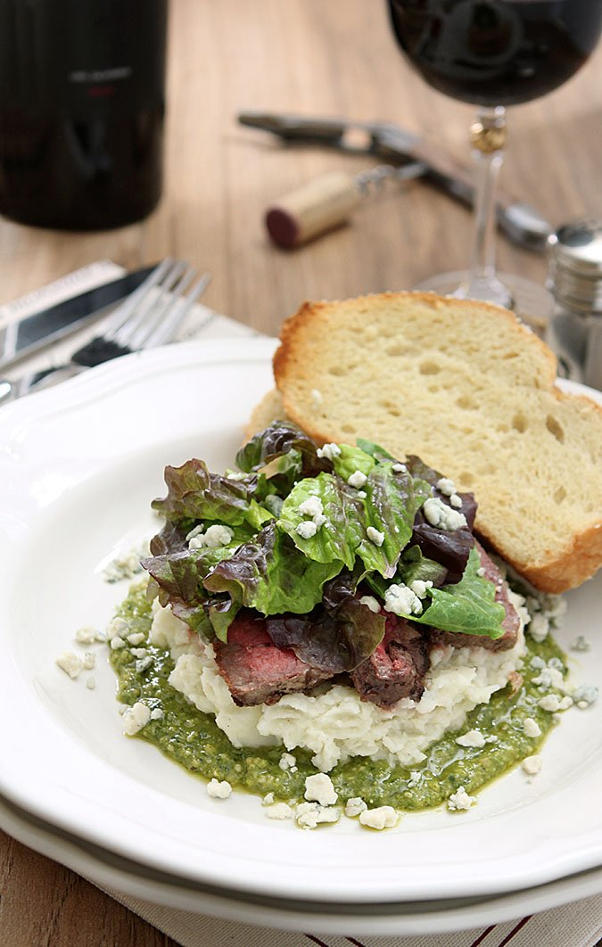 Flank Steak Salad with Mashed Potatoes, Pesto and Gorgonzola Cheese on a White Round Plate