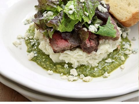Flank Steak Salad with Mashed Potatoes, Pesto and Gorgonzola Cheese Served on a White Plate