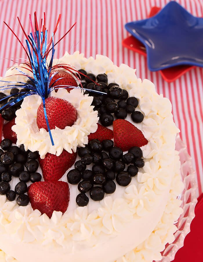 Fresh Strawberry & Blueberry Poke Cake Decorated with Fresh Berries and Real Whipped Cream