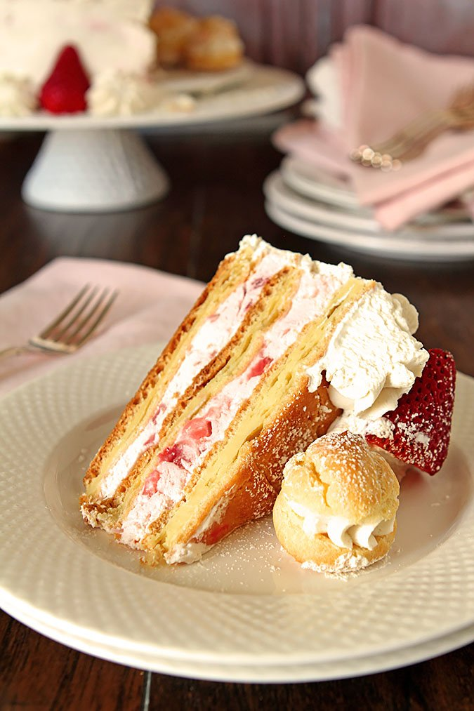 Slice of Strawberry Cream Puff Cake Served on a White Round Plate