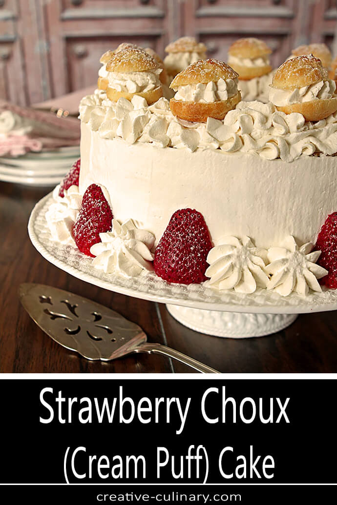 Strawberry Cream Puff Cake on White Cake Stand and Decorated with small Cream Puffs and Strawberry Halves