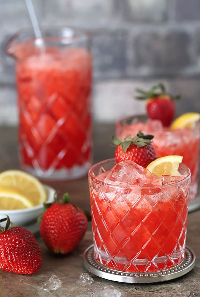 Strawberry Lemonade and Ginger Beer Fizz Cocktail in Glasses with a Serving Pitcher