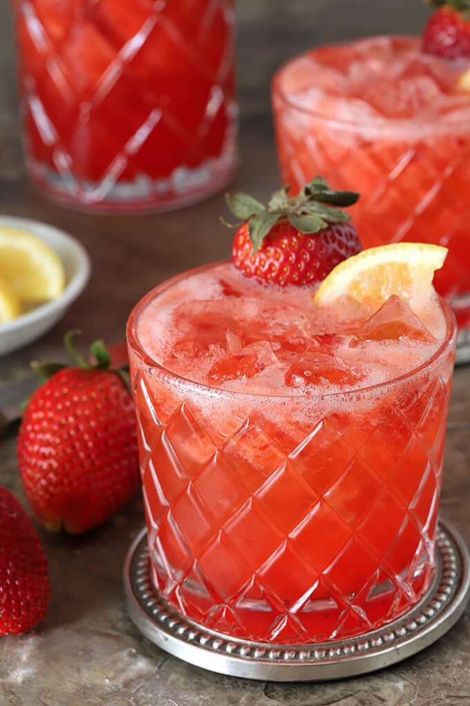 Strawberry Lemonade and Ginger Beer Fizz Cocktail in a Glass with Lemon and Strawberry Garnish