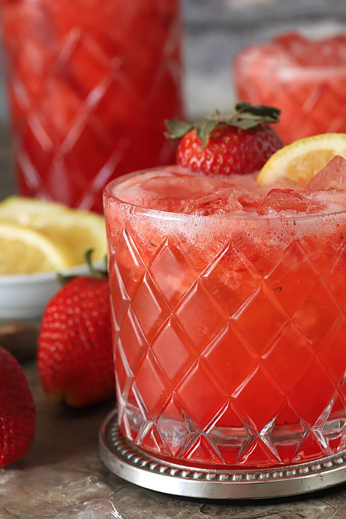 Strawberry Lemonade and Ginger Beer Fizz Cocktail in a Glass with Strawberry and Lemon Garnish