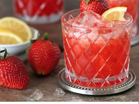 Strawberry Lemonade Fizz Cocktail served in a lowball glass and garnished with lemon.