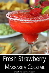 A Fresh Strawberry Margarita in Margarita Glass Garnished with Lime and a Strawberry