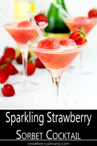 Sparkling Strawberry Sorbet Cocktail Served in a Champagne Glass and Garnished with Fresh Strawberries