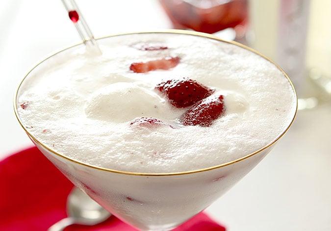 Strawberry Prosecco Float Cocktail closeup of vanilla ice cream and strawberries in gold rimmed martini glass.