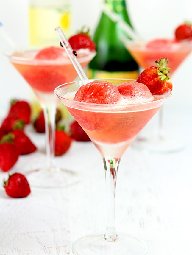Sparkling Strawberry Sorbet Cocktail served in a martini glass with a straw.