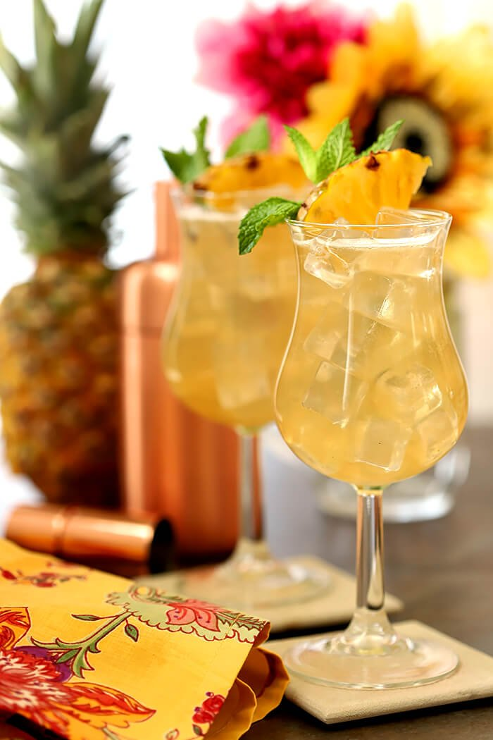Tahiti Vanilla Sky Vodka Cocktails Garnished with Pineapple Wedges and Mint