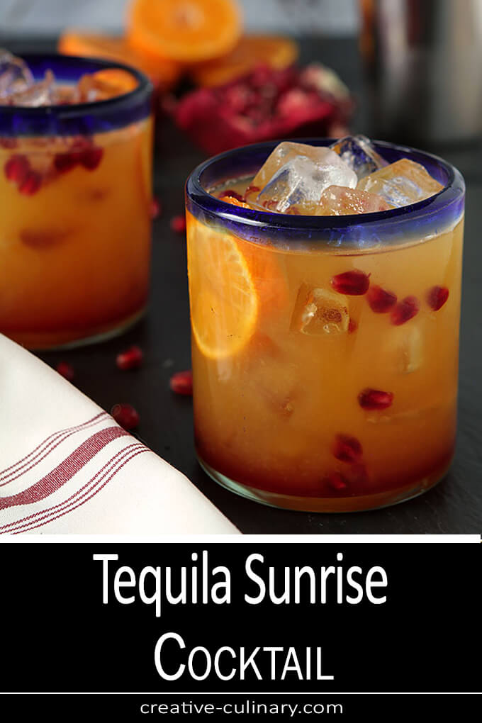 Tequila Sunrise Cocktail in a Glass with a Blue Rim; garnished with Pomegranate Arils