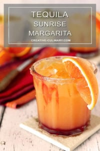 Tequila Sunrise Margarita Garnished with a Sugar Rim and an Orange Wedge