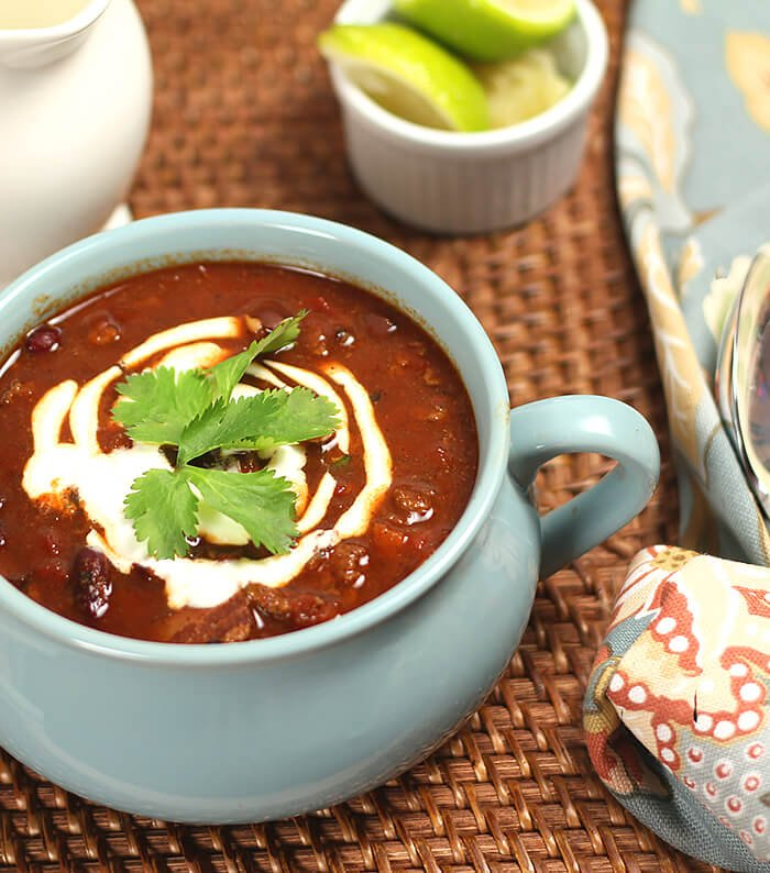 Three Bean Chili in a Blue Crock with Sour Cream and Lime Garnish